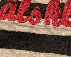 Grå, svart och röd haklapp med broderad text från Lundmyr of Sweden