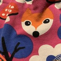 Rosa haklapp med färgglatt mönster av rävar, svampar, träd och blommor från iELM