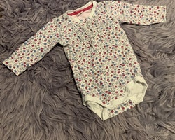 Vit body med rosa och blå blommor och ljusrosa byxor från Lindex stl 68