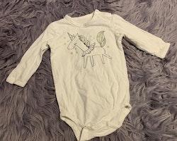 Tredelat set med vit body med en enhörning i svart och silver, vita leggings med glittriga silver stjärnor och en ljusgrå glittrig tyllkjol från My wear stl 68