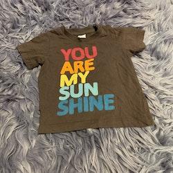 Brun t-shirt med färgglatt text tryck och grå tunna byxor som kan vikas till shorts från HM stl 68