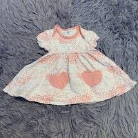 Kortärmad vit klänning med rosa mönster och hjärtformade fickor från PoP stl 68