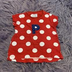 Röd t-shirt med vita prickar och ett blått A med små vita prickar från PoP stl 68