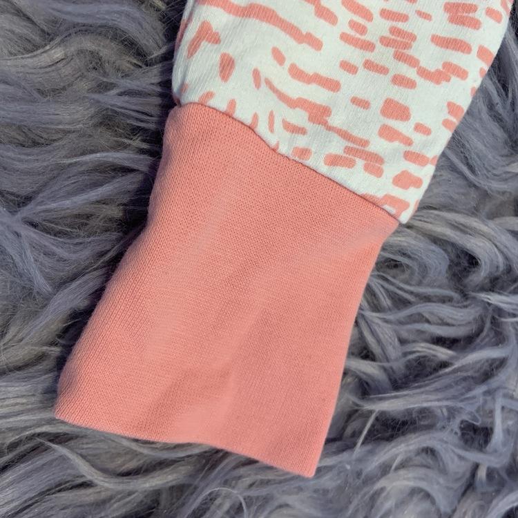 Öron försedd vit jumpsuit med rosa fläckar, kantband och muddar från PoP stl 68