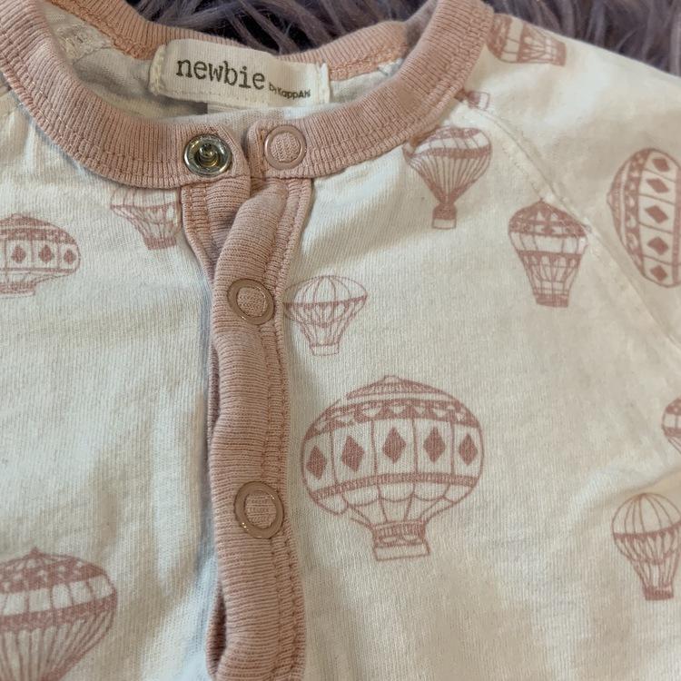 Vit kortärmad och kortbent pyjamas med ljusrosa kantband och mönster av luftballonger från Newbie stl 62