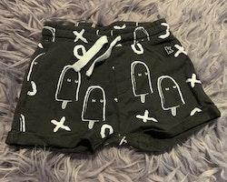Svarta shorts med vitt glass och bokstavsmönster från Kaxs stl 68