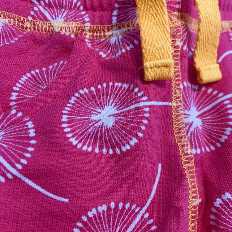 Starkt rosa shorts med vitt maskros mönster och gula detaljer från Maxomorra stl 62/68