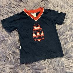 Mörkblå t-shirt med detaljer såsom ett ankare i rött och vitt från Lingon & Blåbär stl 70