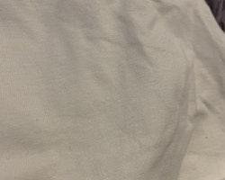 Cremefärgad body med svarta rosetter på axlarna från Åhléns stl 62/68
