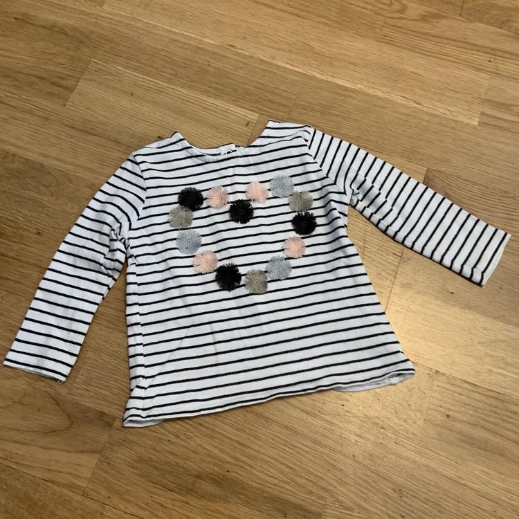 3 delat paket med tröjor; en rosa med svart stänk, en vit med svarta ränder och små pompom bollar samt en ljusturkos tröja med färgglatt enhörningsmönster från NeXT stl 74