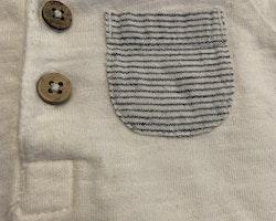 Vit kortärmad body med farfarsknäppning och mörkblå randig ficka från Newbie stl 56