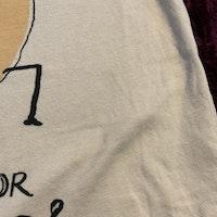 Beige t-shirt med mörkgrå ärmar och ett korv och text tryck från Nadadelazos stl 2-4 år