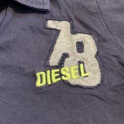 Mörkblå piké med ljusgrå melerade detaljer och gult textbroderi från Diesel stl 104
