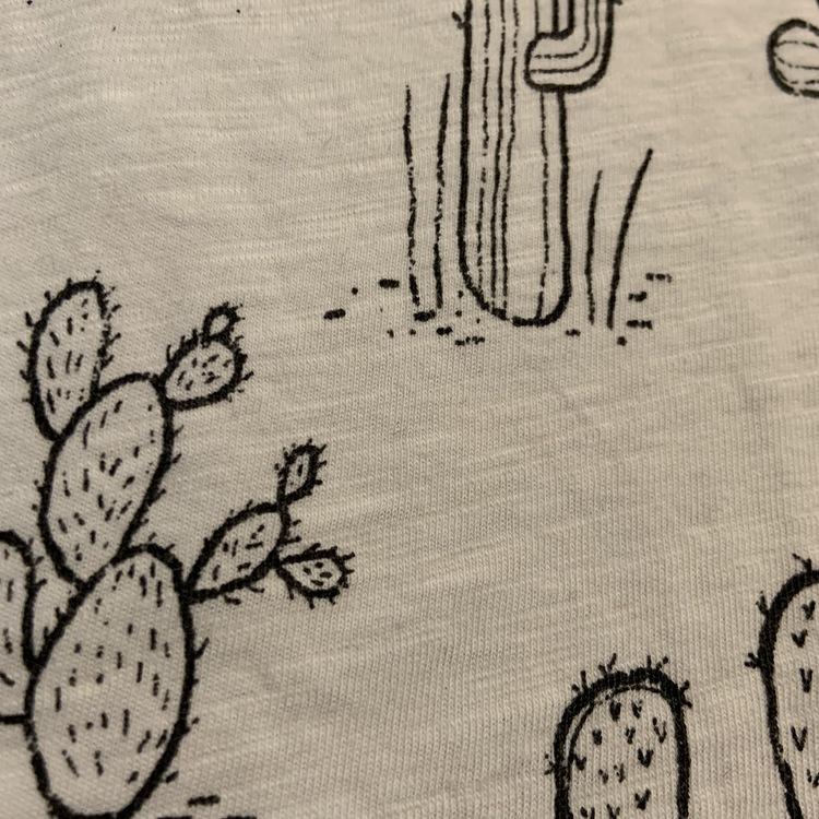 Vit t-shirt med svarta kaktusar, bröstficka och gult texttryck från Lindex stl 98/104