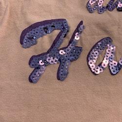 Persikofärgad topp med lila paljett text från Sweet heart stl 98/104