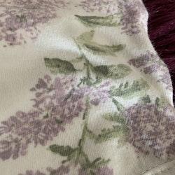 Vit ärmlös body med lila och grönt syren mönster och vita volanger från Newbie stl 56