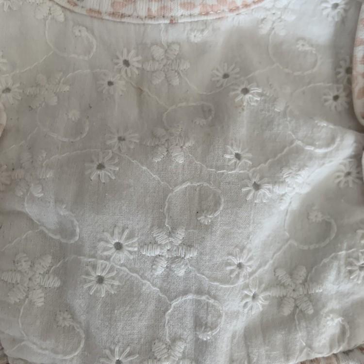 Vit klänning med rosa och grönt blommönster, volanger, vit spets och vitt hålbroderi från Newbie stl 68