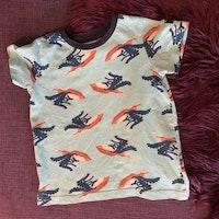 Ljusblå t-shirt med blått, svart, orange och vitt mönster av krokodil på jetski från PoP stl 104