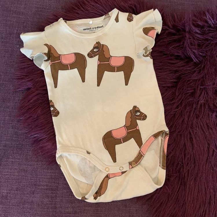Beige kortärmad body med volangärmar och häst mönster från Mini Rodini stl 68-74