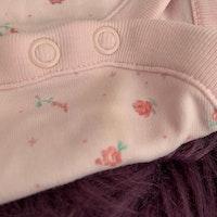 En rosa och en vit kortärmad body med smått blommönster från NeXT stl 62/68