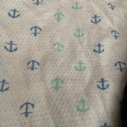 En mörkblå och en vit ärmlös body med marint mönster från Lupilu stl 62/68
