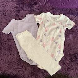 3 delat paket med ljuslila kortärmad omlottbody, vit kortärmad omlottbody med rosa och lila marint mönster samt beigea leggings från Lupilu stl 62/68