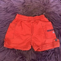 Röda shorts med svarta sömmar och blått text broderi på en ficka från Sweet Cherry stl 3-6 mån