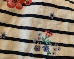 Vit jumpsuit med svarta ränder, fickor samt rosa och blå blommönster från HM stl 98/104