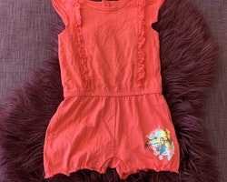 Rosa jumpsuit med volanger och ett litet fågel och blomtryck från Lupilu stl 74/80