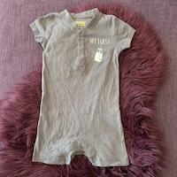 Jumpsuit i grått med vitt texttryck och ett mjölkglas från Lupilu stl 74/80
