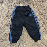 Mörkblå träningsbyxor med blå detaljer från Adidas stl 74