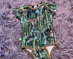 Kortärmad body i främst gröna och bruna nyanser med kaktusar och kattdjur från Molo stl 62