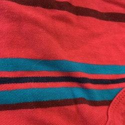 Kortärmad pikébody i främst rosa med ränder i brunt, blått, orange och svart från Tommy Hilfiger stl 3-6 mån