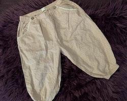 Vita tunna byxor med rosa mönster, fickor med spets och dekrativa knappar från Newbie stl 74