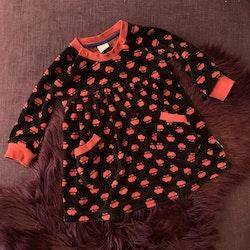 Mörkbrun velourklänning med fickor och röda kantband/muddar samt blommönster från PoP stl 80