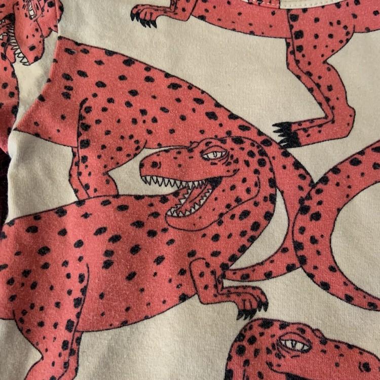 Beige kortärmad body med rosa dinosaurier från Mini Rodini stl 80/86