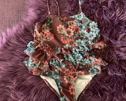 Brun baddräkt med blommor i olika rosa och blå nyanser från Mini Rodini stl 92/98