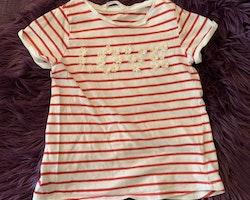 Vit topp med röda ränder och tygblommor i vitt och rosa som stavar LOVE från HM stl 110/114e
