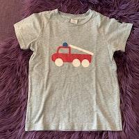 Gråmelerad t-shirt med stiliserad brandbil i vitt, rött och blått från PoP stl 110/116