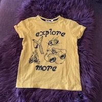 Gul t-shirt med svart text- och bildtryck från Kappahl stl 110/116