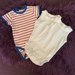 3 delat paket med en kortärmad vit body med blå kantband och röda ränder samt två vita linnesbody från Kaxs stl 68 + 62