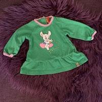 Set med grön tunika med ljusrosa kantband och Bamsetryck samt flerfärgade bredrandiga leggings från Lindex stl 62