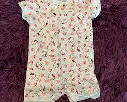 Ljust turkos kortärmad och kortbent pyjamas med främst rosa, vitt och grönt Hello Kitty mönster från HM stl 62