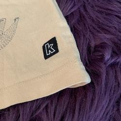 Aprikosfärgat set bestående av en t-shirt med mörkgrått sengångaretryck och leggings med mörkgrått lövmönster från Kaxs stl 68