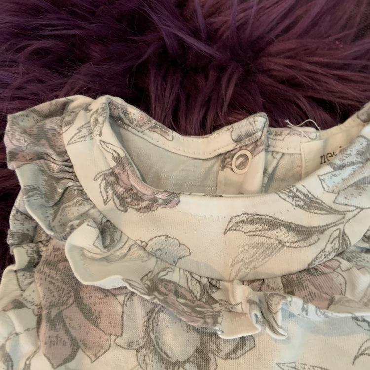 Vit ärmlös klänning med blommönster i mörkgrått, pastellblått och lila från Newbie stl 62