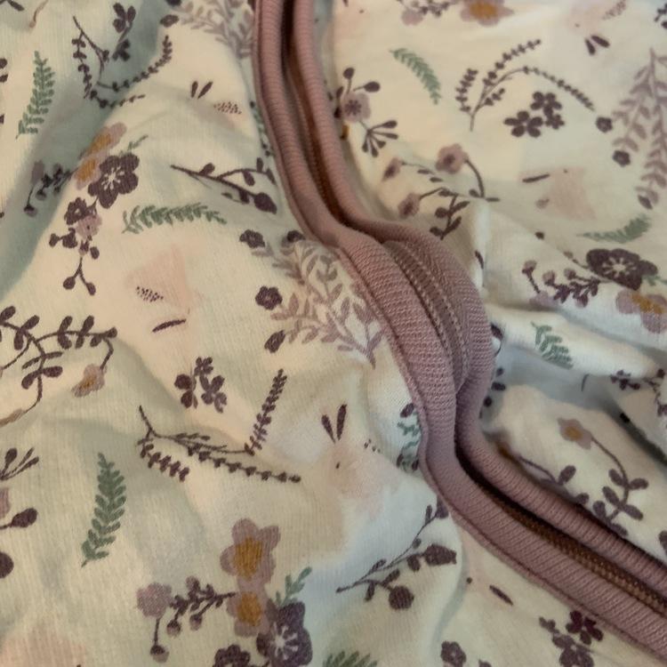 Vit jumpsuit med ljuslila dragkedja/kantband och mönster av blommor och kaniner i främst lila nyanser från Ellos stl 62