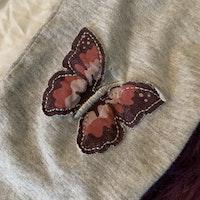 Set med vit body med rosa och lila fjärilsapplikationer och grått texttryck samt grå leggings med fjärilar på knäna från Lindex stl 74
