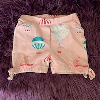 Ljusrosa shorts med flerfärgade luftballonger, fickor och rosetter från Livly stl 2 år