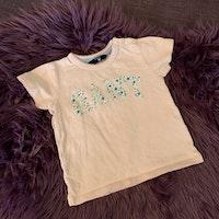 Ljusrosa t-shirt med texttryck i vitt med blå blommor från Gant stl 74