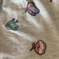 Gråmelerad topp och kjol med mönster i olika färger, tex grodor, fåglar och nycketpigor från HM stl 92